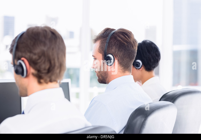 Business colleagues with headsets in a row - Stock Image