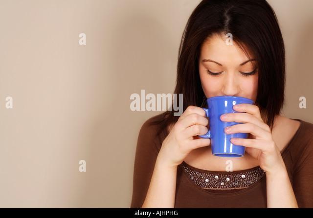 Woman drinking a hot drink - Stock-Bilder