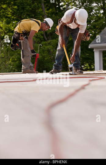 Carpenters working on particle board with power cord in foreground - Stock Image