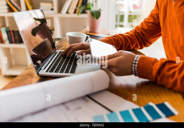 Close-up of man using phablet and laptop at desk with color samples - Stock Image