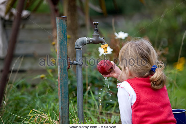 A young girl washing an apple under an outdoor tap - Stock Image
