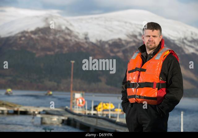 Worker smiling on salmon farm - Stock Image
