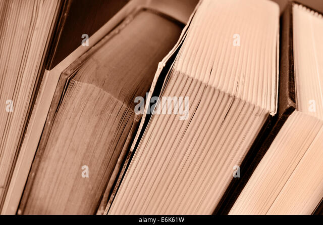 closeup of some books, in sepia tone - Stock Image