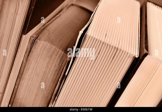 closeup of some books, in sepia tone - Stock Image
