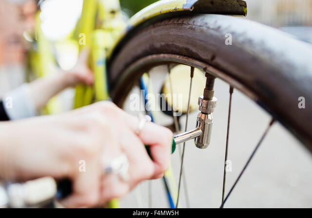 Cropped image of woman's hand inflating bicycle tire on sidewalk - Stock-Bilder