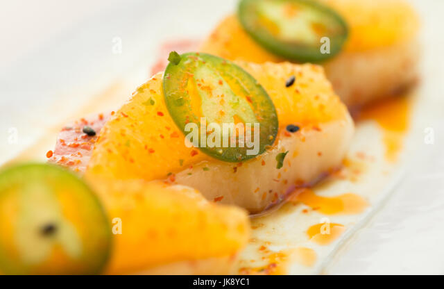 Close up of specialty high end Yellowfin tuna sushi roll with jalapeno on plate ready to eat. - Stock Image