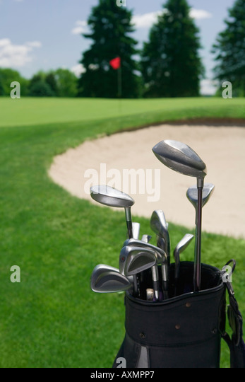 Golf clubs with course and sand trap in distance - Stock Image