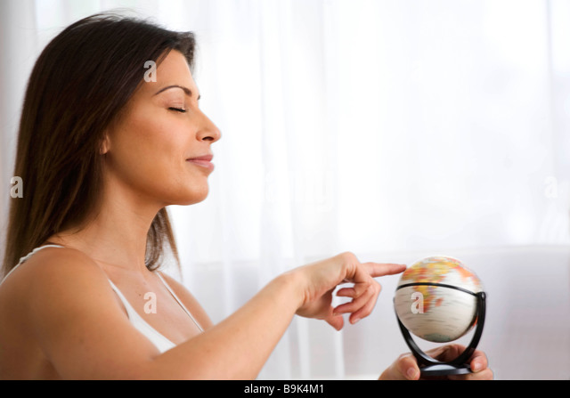 Woman looking for location on a Globe - Stock Image