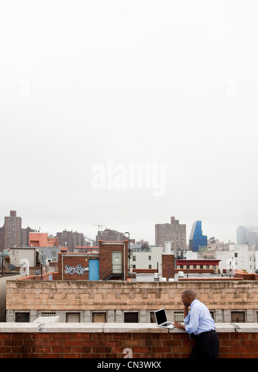 Businessman using laptop on roof - Stock Image