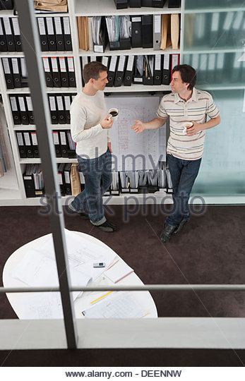 Two businessmen holding coffee in office - Stock Image