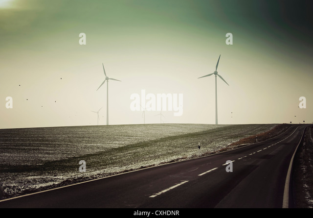 Germany, Saxony, View of empty road with wind turbine - Stock Image
