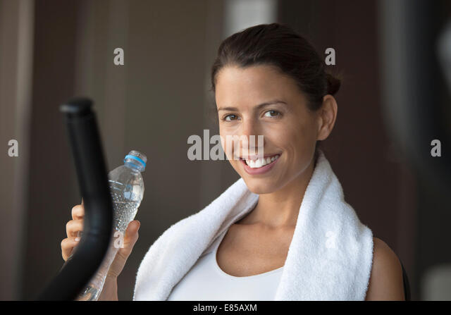 Woman hydrating with bottled water in health club - Stock Image