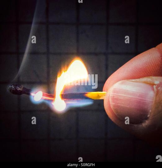 Hand holding burning match stick - Stock Image