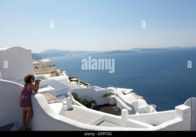 A woman takes a photograph in the town of Oia on the hot and sunny Greek island of Santorini - Stock Image