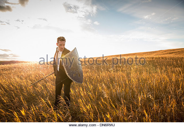 Aggressive businessman with sword and shield in field - Stock Image
