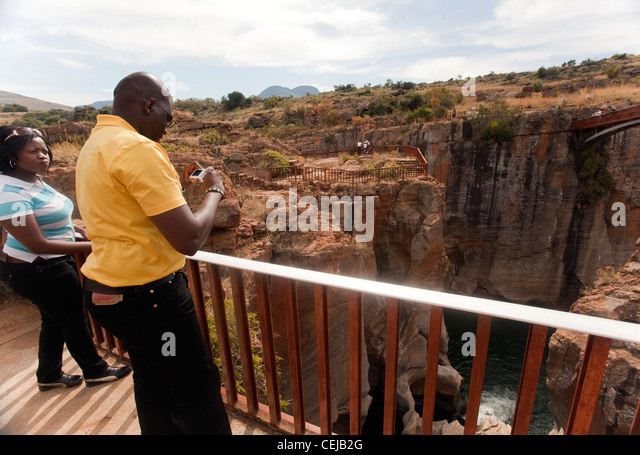 Tourist at observation point taking photos of Bourkes Luck Potholes,Mpumalanga - Stock Image