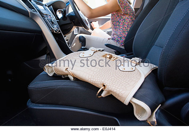 Female Driver Leaving Handbag In Car As She Gets Out - Stock Image