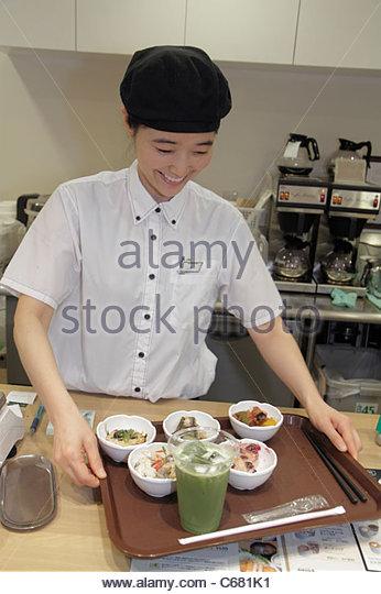 Tokyo Japan Shinjuku Shinjuku NS Building restaurant buffet Asian woman cashier uniform worker food tray drink - Stock Image