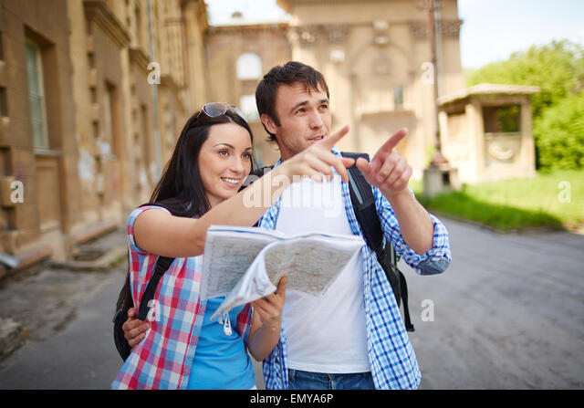 Young travelers with paper guide spending leisure in foreign town - Stock Image