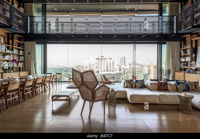 Spacious double-height living area with views of Beirut. The pentagonal shaped caned armchair is by Philippe Bestenheider - Stock Image