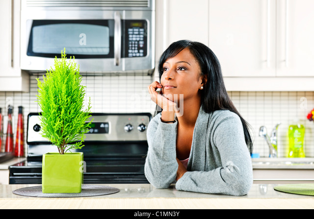 Thoughtful black woman in modern kitchen interior - Stock Image
