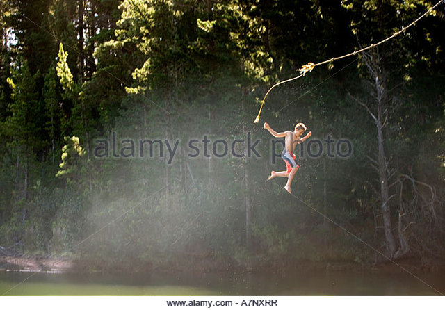 Boy 9 11 in swimming shorts letting go of rope swing above lake side view - Stock-Bilder