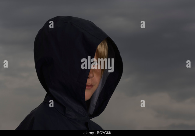 Boy with face partially obscured by jacket hood, looking at camera - Stock Image