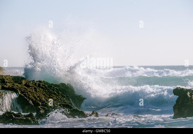 A wave in a stormy ocean smashing against a rock with splash and foam. - Stock Image