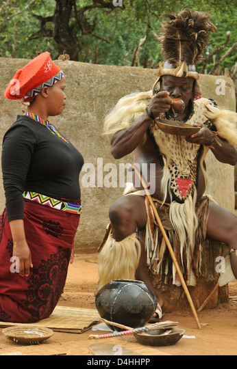 Zulu chief tasting traditional sorghum beer with wife watching Shakaland South Africa ethnicity Cultures Travel - Stock-Bilder