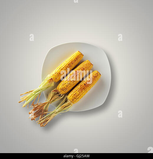 Whole Grilled Sweet Corn on a white plate and table from above - Stock Image