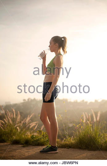 Young woman outdoors, taking  break from workout, drinking water from bottle - Stock-Bilder
