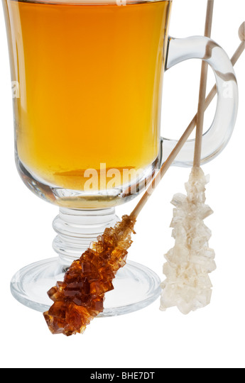 Cup of tea with sweet caramel sugar on wood sticks close-up over white. - Stock Image