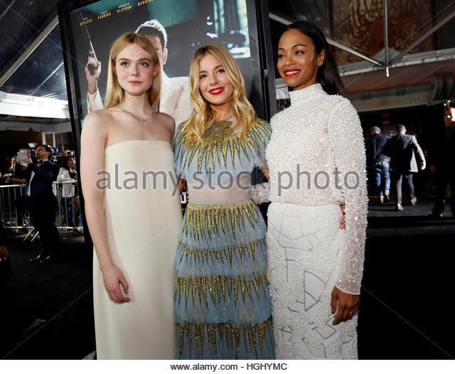 Cast members Elle Fanning (L), Sienna Miller (C) and Zoe Saldana pose at the premiere of 'Live by Night' - Stock Image