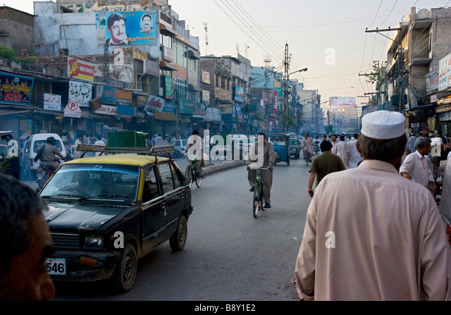 Street scene with pedestrians old buildings pollution and vehicles, Rawalpindi, Pakistan - Stock Image