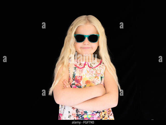 Young girl with long blonde hair wearing sunglasses, smiling - Stock Image