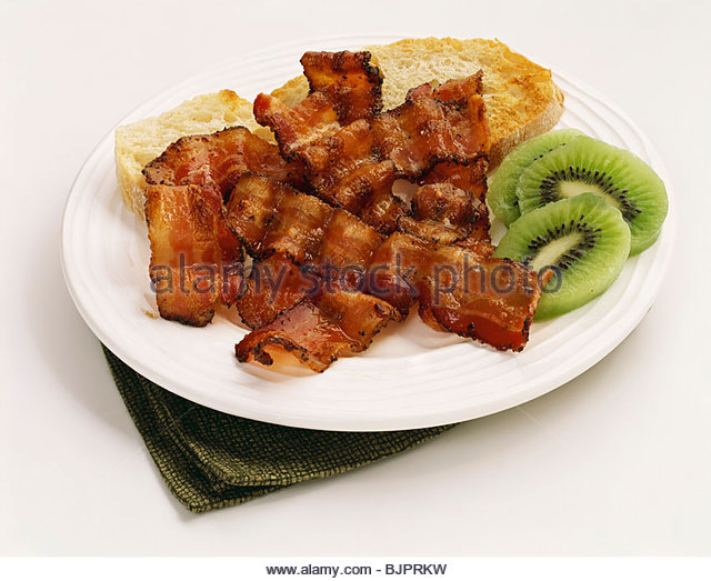 Fried Bacon Strips with Toast and Kiwi Slices - Stock Image