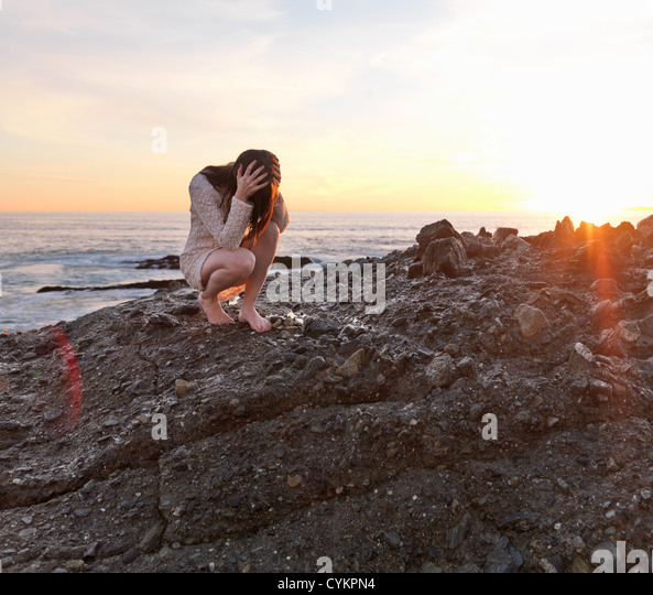 Woman holding her head on rocky beach - Stock Image