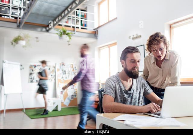 Design professionals working at laptop in office - Stock-Bilder