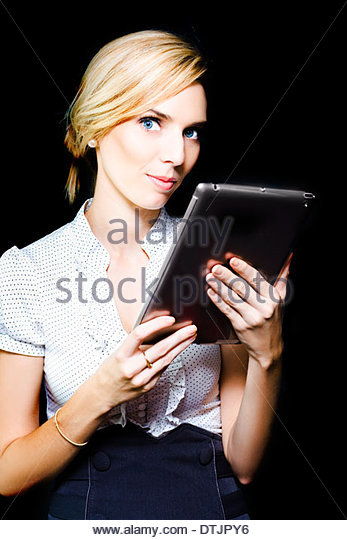 Beautiful stylish professional blonde woman holding a touch screen tablet with the screen facing herself and looking - Stock Image