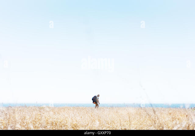 A hiker walks through a stretch of grass as part of Northern California's Lost Coast. - Stock Image