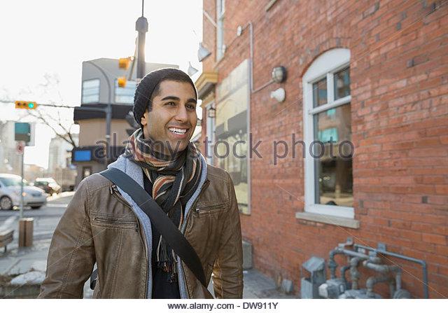 Happy man standing on city street - Stock Image