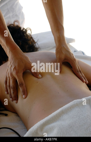 A man practicing a deep tissue massage on a woman back - Stock Image