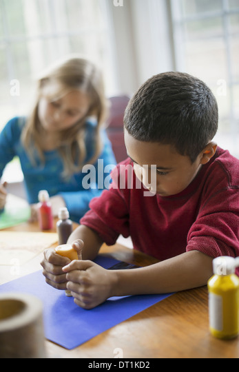 Children in a family home Two children sitting at the table using paint and paper to create decorations - Stock Image