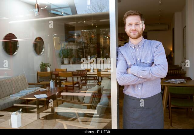 Portrait of young male cafe owner with arms folded in doorway - Stock Image