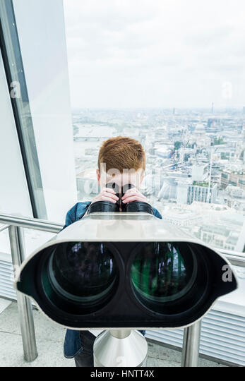 A boy looking through binoculars from a viewing platform. - Stock Image