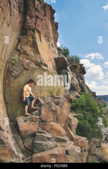 Boy climbing rocks - Stock Image