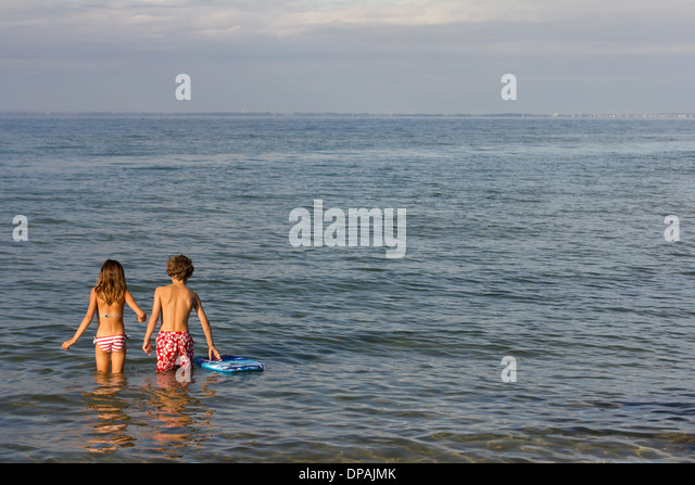 Brother and sister paddling in sea - Stock Image