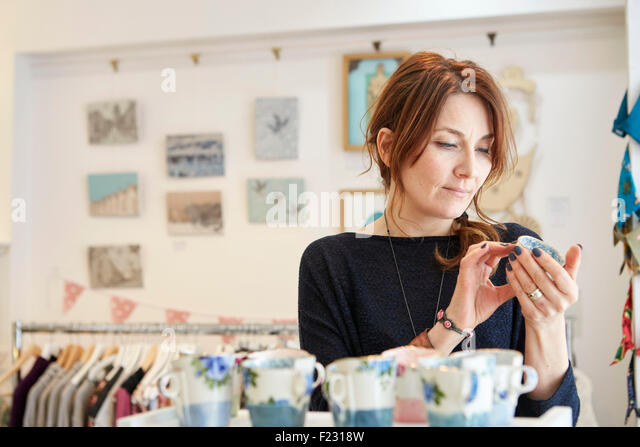 A mature woman in a gift shop holding a small china cup in her hands. - Stock Image