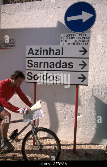 Portugal Algarve Alte cyclist bicycle male reads map signs directions - Stock Image