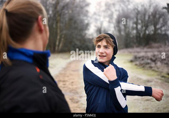 Teenage boy stretching arm, looking at mother smiling - Stock Image